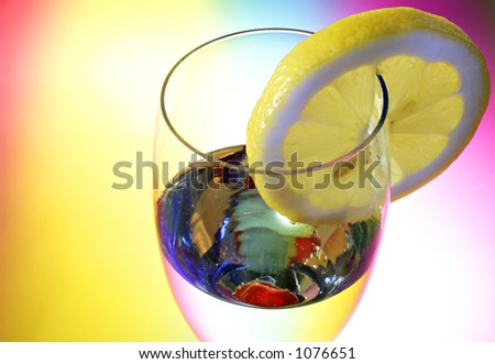 Glass of champagne with a cherry and a lemon - stock photo