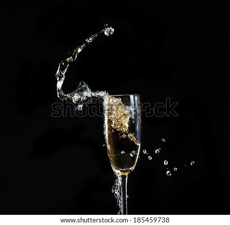 Glass of champagne with splash, on black background