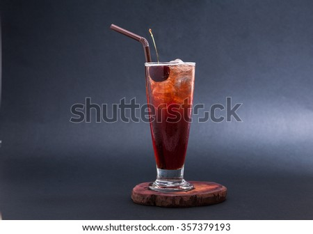 Glass of cherry juice on black background