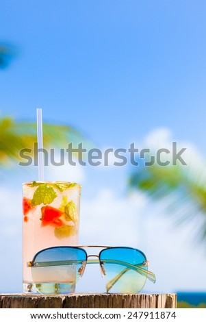 glass of chilled cocktail mohito and sunglasses on table near the beach - stock photo