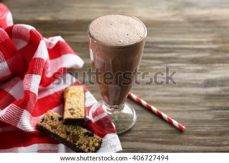 Glass of chocolate milkshake and cookies on wooden background - stock photo