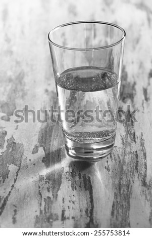 Glass of clean mineral water on old color wooden background - stock photo