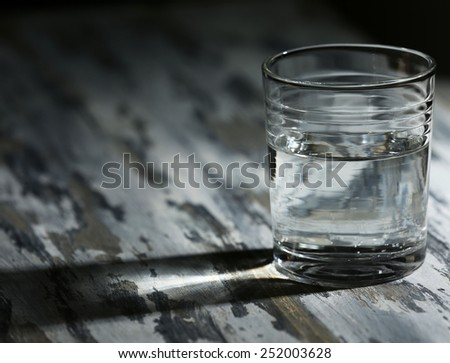 Glass of clean mineral water on old color wooden surface and dark background - stock photo