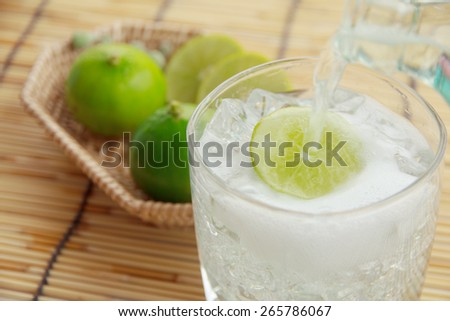 glass of clean water with ice cubes and green leaves of mint