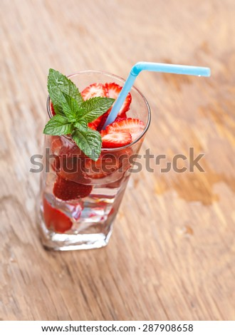 glass of cocktail and berries closeup on wooden background