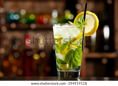Glass of cocktail in bar on bright blurred background - stock photo