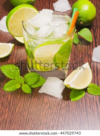 Glass of cocktail mojito, lime, mint leaves and ice on dark wooden background