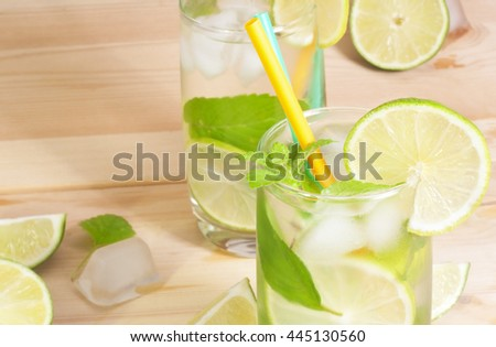 Glass of cocktail mojito, lime, mint leaves and ice on wooden background