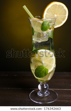 Glass of cocktail with lemon and mint on table on dark yellow background