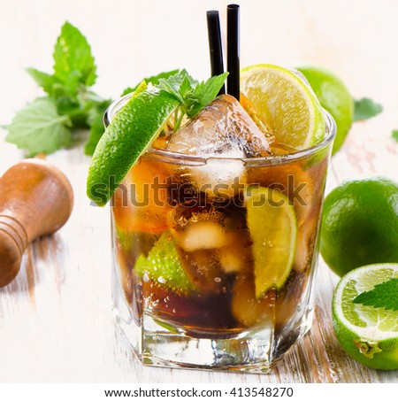 Glass of cocktail with rum, lime, mint  and ice. Selective focus - stock photo