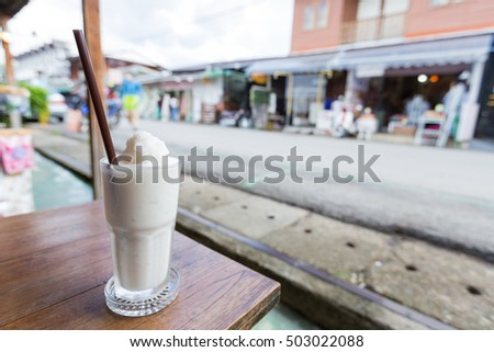 Glass of coconut juice smoothie Is placed on a wooden table along the corridor.