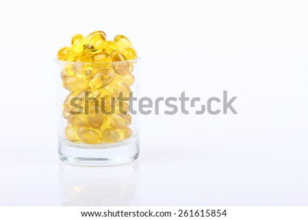 glass of Cod liver oil omega 3 gel capsules,Vitamin capsules isolated on pastel background. - stock photo