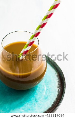 Glass of coffee with milk and coffee beans on rustic wooden table, Selective focus