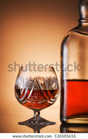 Glass of cognac and bottle close up