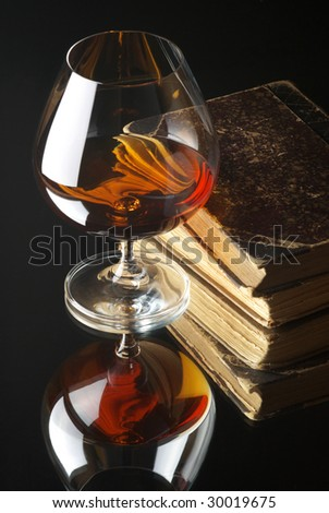 Glass of cognac and old books with reflection on black background.