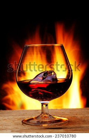 glass of cognac in front of the fireplace - stock photo