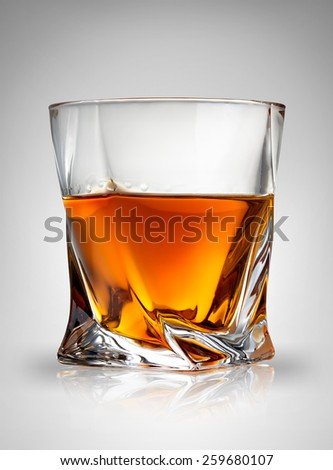 Glass of cognac on a gray background