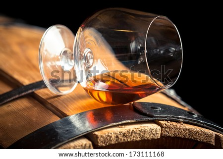 Glass of cognac on the old barrel - stock photo