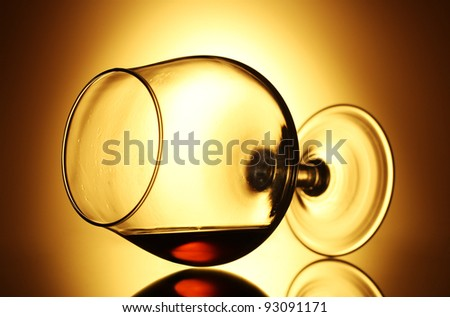 Glass of cognac on yellow background - stock photo