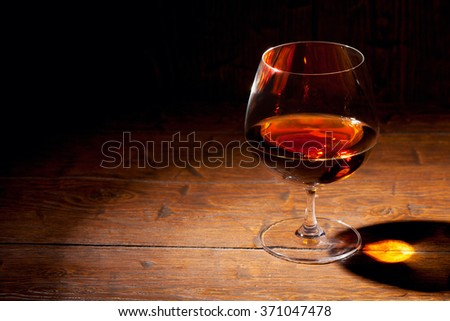 Glass of cognac with lemon on old wooden background - stock photo
