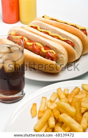 glass of cola, french fries and three classic hot dogs with mustard and ketchup on a plate - stock photo