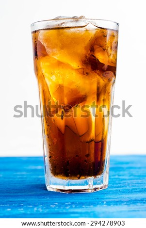 Glass of cola on the wooden background