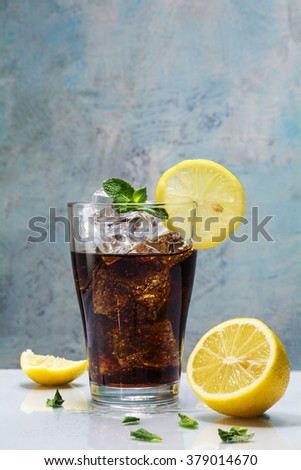 glass of cola or coke with ice cubes, lemon slices and peppermint garnish against a blue vintage wall,  copy space, selected focus  - stock photo
