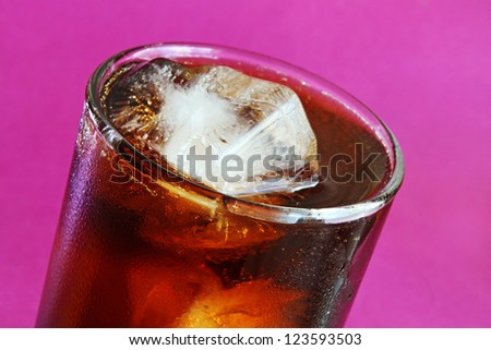 Glass of Cola with ice cubes on a purple background