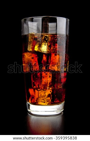Glass of cola with ice cubes on black wooden desk