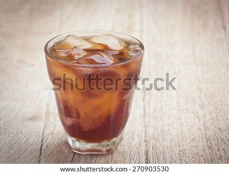 glass of cola with ice cubes on wood - stock photo