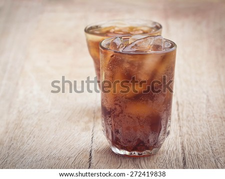 glass of cola with ice cubes on wood