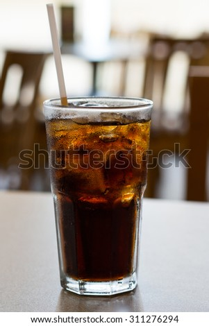 glass of cola with ice on a table - stock photo