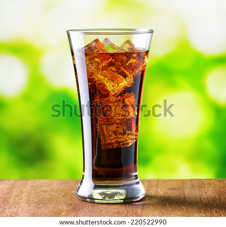 Glass of cola with ice on nature background.
