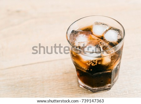 glass of cola with ice on the table