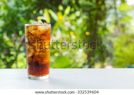 glass of cola with on wooden table in garden background. - stock photo