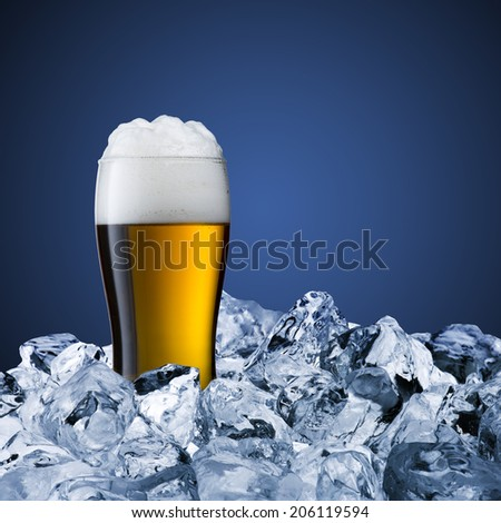 Glass of cold beer on ice cubes - stock photo