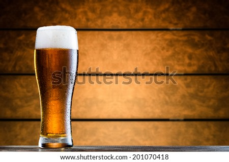 Glass of cold beer on wooden table