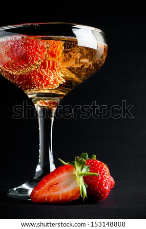 Glass of cold champagne with strawberries on a black background, close-up - stock photo
