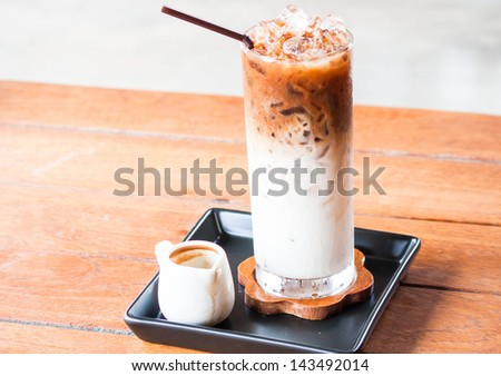 Glass of cold coffee latte with espresso pitcher - stock photo