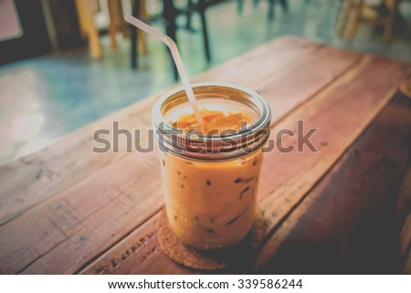 Glass of cold coffee on brown wood table - Vintage style effect picture - stock photo