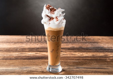 Glass Of Cold Coffee With Whipped Cream On Wood, Black Background. - stock photo