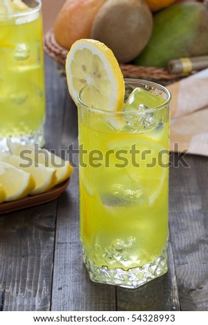 Glass of cold lemon cocktail with ice cubes on wooden table top