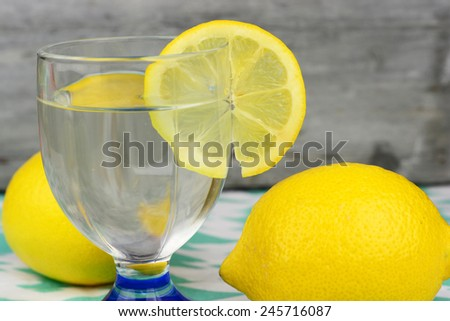 glass of cold or hot lemon water on a colored doily