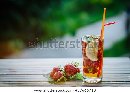 Glass of cold tea with mint,strawberry,lemon, on table, on green background,soft focus. - stock photo
