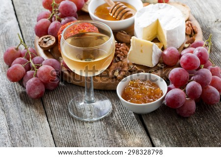 glass of cold white wine and snacks on a wooden table, top view