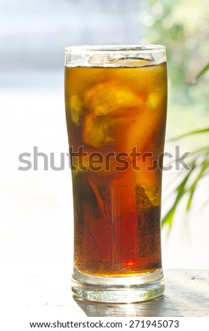 Glass of cool soft drink in nature light