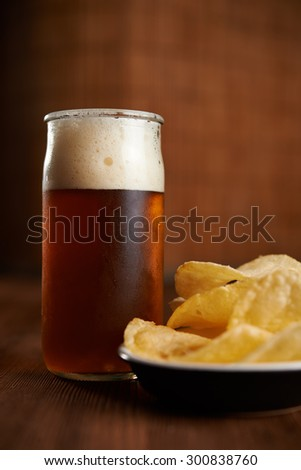 glass of craft beer and potatoes chips on wooden background - stock photo