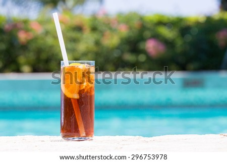Glass of Cuba Libre on the pool nosing at the tropical resort. Horizontal, cocktail on left side - stock photo
