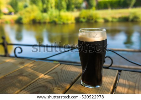 Glass of dark beer on an outdoor wooden patio table