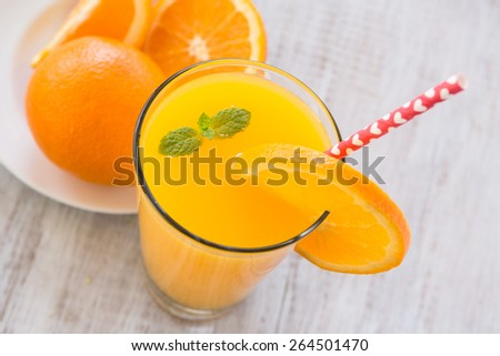 Glass of delicious fresh orange juice for breakfast with a heart straw - stock photo
